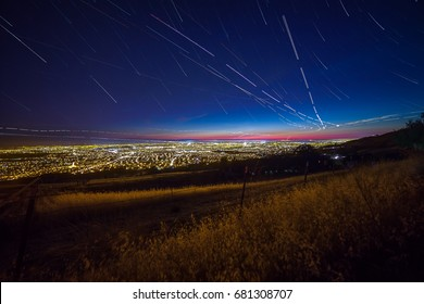 View of the Silicon Valley from Mount Hamilton at night with stars and plane trails.
