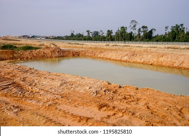 A view of a silt trap on the construction site. A silt trap is a designated area where water that is contaminated with suspended sediment can settle to the bottom of the trap until it can be removed.