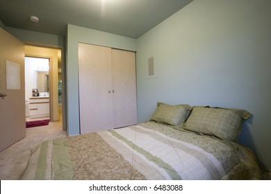 View of simple bedroom with bathroom through door