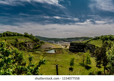 View of Sint Pietersberg or mount Saint Peter (the Dutch canyon) with green vegetation, the old marl quarry with cement factory in the background, sunny day with a blue sky in Maastricht in the Nether
