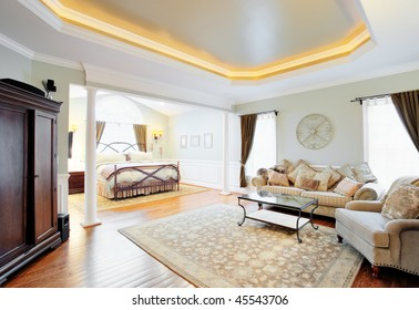View of a sitting area and bed in a master suite with coved ceiling. Horizontal format.