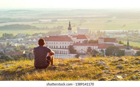 View of sitting young tourist man overlooking beautiful Mikulov castle from the top of Saint Hill while sunset. South Moravia, wine region in the Czech Republic.