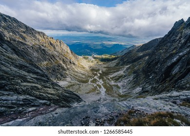 View of a Skalnate pleso lake in High Tatras (Vysoke Tatry), Slovensko. Deep alpine like valley in mountain landscape of Vysoke Tatry. Skalnate pleso and a cable car lift to Lomnicky stit.