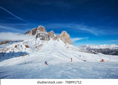View of a ski resort piste with people skiing in Dolomites in Italy