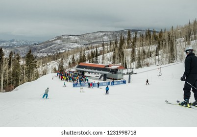 View of ski slope with skiers sking down to the chairlift; Steamboat Springs, Colorado on winter day; pine trees on the background