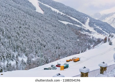 View of ski slopes and the parking of cars at a slope. Ski slopes between fir-trees, there are a lot of snow, trees in snow