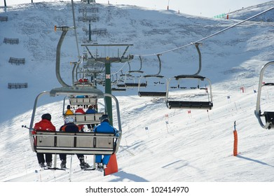View of the ski slopes and people on chair lifts on winter sunny day