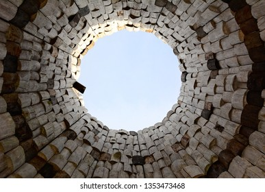 View of the sky in the form of a circle from the bottom up inside a round tower of wooden bars.