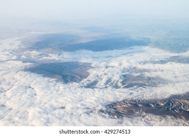 View of the sky and mountains on earth from the window of the airplane
