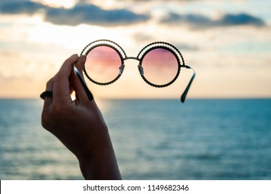 The view of the sky and the sea in pink glasses. Rose-colored sunglasses in female hand. Optimism concept