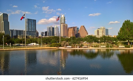 a view of the skyline of Austin Texas near sunset as reflected in an artificial pond