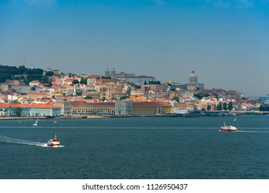 View of the skyline of the city of Lisbon with boats (cacilheiros) on the Tagus River; Concept for travel in Portugal and visit Lisbon
