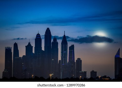 View of the skyline of Dubai in the evening, crossroad with clouds and cars, palaces in the background, memories of a day in United Arabian Emirates, amazing city in middle-east of Asia, holiday place