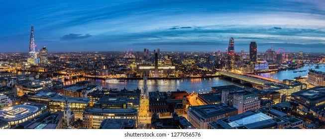 View to the skyline of London by night: from Tower Bridge along the Thames river to Westminster Palace