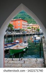 view of the small boat harbor in Nago-Torbole through the arch, Lake Garda, Italy
