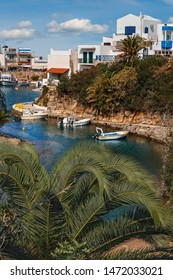 view of small boats in the harbor, through the leaves of a palm forest at the Greek fishing village of Sissi