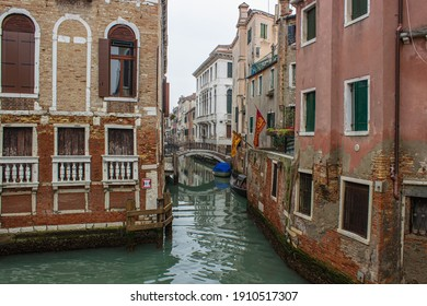 View of a small canal in Venice with old houses with Venetian flags. Gloomy winter day.
