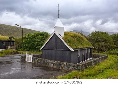 View of a small church, on the Faroe Islands. Typical is the wooden construction and the grass-covered roofs. It is a rainy day, as so often in the north.