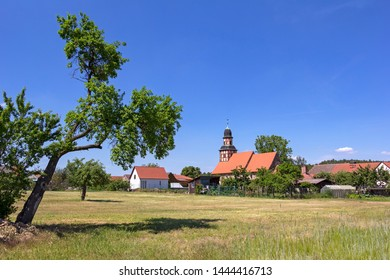 View of the small half-timbered church in the village of Raben, Hohen Flaeming, Brandenburg. In the foreground you can see a agriculture field.