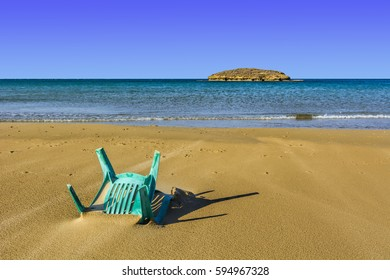 View of a small island from the Israeli shore of the Mediterranean Sea. Plastic chair buried in the sand of beach in Israel.