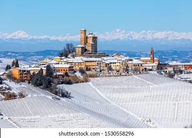 View of small medieval town and vineyards on the hill covered in snow under blue sky in Piedmont, Northern Italy.