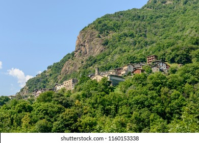 view of small mountain village on steep green slope, shot on a bright summer day at Perloz,  Lys valley, Aosta, Italy