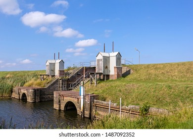 View of a small and old lock on a river flowing into the North Sea. Seen on the western coast of Denmark. Hojer Sluse