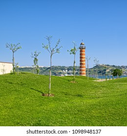 A view of small park with new trees on curved land and with old lighthouse on the background, located in Belem district of Lisbon city, Portugal.