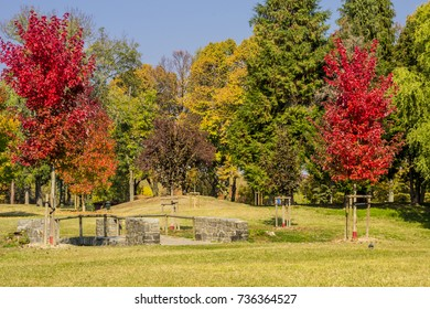 View of a small stone bridge between the tree foliage in autumn in a public park in Turin (Piedmont, Italy).