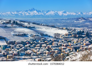 View of small town of Alba, hills and mountains on background covered in snow in Piedmont, Northern Italy.