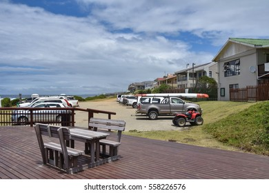 A view of the small town of Kei Mouth with a bench, vehicles and some houses in the Eastern Cape on the Garden Route in South Africa at the Indian Ocean