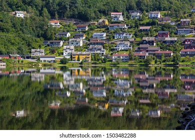 View to the small town Norheimsund. The houses are reflected in the calm water of the lake Movatnet. Norway, Hardangerfjord.