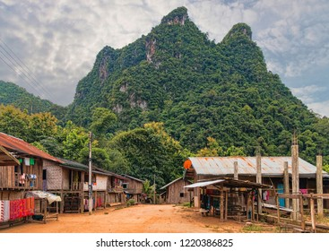 View of Small Traditional Ethnic Minority Village in Laotian Rainforest with View of Limestone Mountain Peaks in Distance. Village Center. No People. (Sop Chem Weaving Village Near Muang Ngoi, Laos).