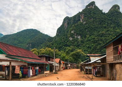 View of Small Traditional Ethnic Minority Village in Southeast Asian Rainforest with View of Limestone Mountain Peak in Distance. Village Main street. (Sop Chem Weaving Village Near Muang Ngoi, Laos).