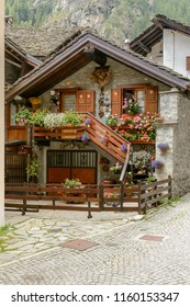 view of  small traditional stone house covered with blossoming flowers, shot on a bright summer day at Gressoney Saint Jean,  Lys valley, Aosta, Italy