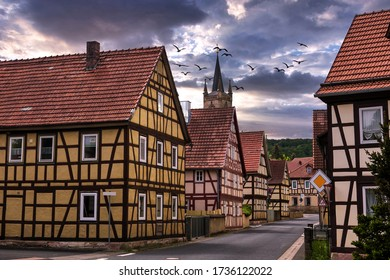 Blick auf die kleine Ortschaft mit Fachwerkhäusern und bewölktem Himmel
