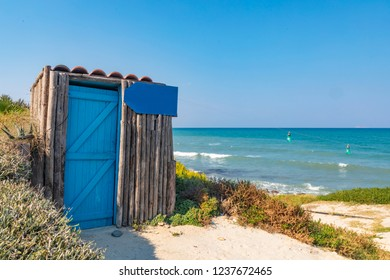 View of a small wooden cabin on the shore of the azure Mediterranean Sea, with a sign that can be used as a placeholder for your own personalised message.