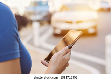 View of a smart phone in the hands of a female requesting a ride share in the city during the day