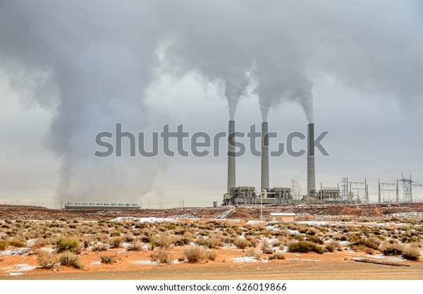 View of smoking smoke stacks of a generating station at the Navajo reservation, Arizona, USA. Desert landscape violated by an air polluting power plant, smog and gloomy sky. Polluting energy source.