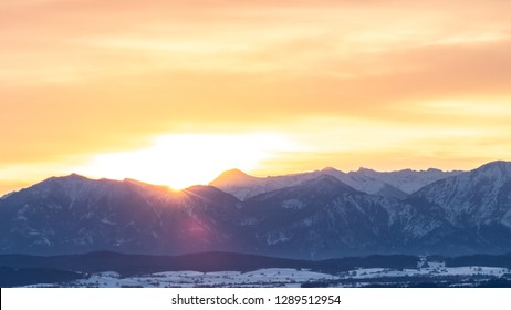 View from the Hohenpeißenberg to the snow covered Alps at sunrise. The sun lights just over the mountains.