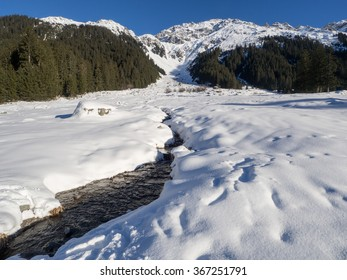 A view of snow - covered landscape  with stream  from the trail of Klosters