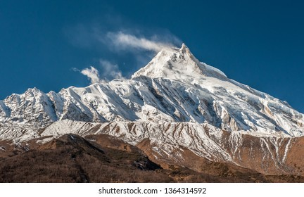 View of snow covered peak of Mount Manaslu (8 156 meters) with clouds in Himalayas, sunny day at Manaslu Glacier in Gorkha District in northern-central Nepal