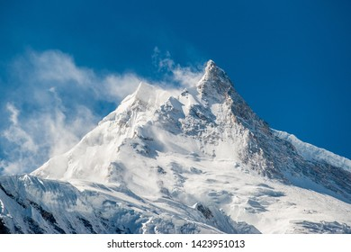 View of snow covered peak of Mount Manaslu (8 156 meters) with clouds in Himalayas, sunny day at Manaslu Glacier in Gorkha District in northern-central Nepal. Detail of snowy peak.