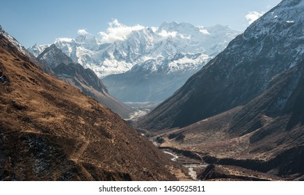 View of snow covered range of Mount Manaslu and valley on the way to pass 8 156 meters with clouds in Himalayas, sunny day at Manaslu Glacier in Gorkha District in northern-central Nepal.