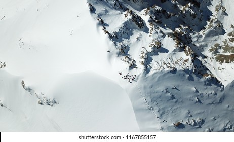 View of the snow top of the mountain from above. Group of climbers at the peak.
