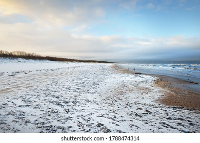 A view from the snow-covered Baltic sea shore at sunset. Riga bay, Latvia. Colorful dramatic cloudscape. Fickle weather, waves and water splashes. Winter tourism, global warming theme