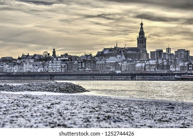 View from the snow-covered beaches and floodplains on the northside of the river Waal towards the city of Nijmegen, the Netherlands and Siant Stephens Church on the hill