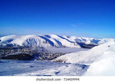 a view of the snow-covered city of Kirovsk and Lake Bolshoy Vudyavr from the northern slope of Mount Aikuainwichor,the BigWood ski resort,the mountains of Khibiny,Kirovsk (Hibinogorsk),Murmansk region