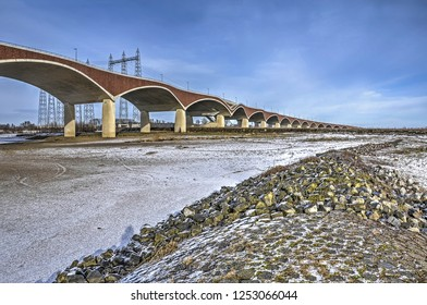 View of the snow-covered floodplain of the river Waal near Nijmegen, The Netherlands with the concrete and brick arches of city bridge De Oversteek (The Crossing) disappearing in the distance