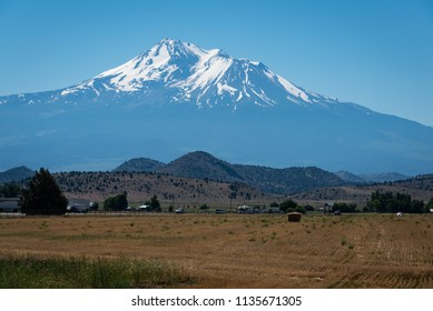 View of snow-covered Mount Shasta and fields in the forefront near Interstate